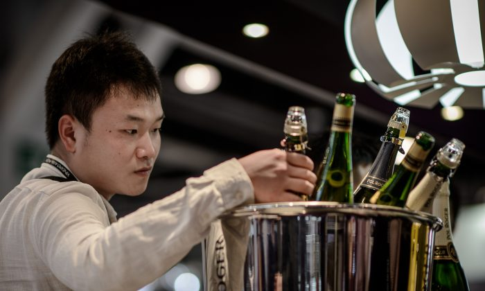 A visitor is checking bottles of Champagne at the Vinexpo Asia Pacific in Hong Kong, on May 27, 2014. On the international financial change, China is very close to pop the Champaign at the end of the year. (PHILIPPE LOPEZ/AFP/Getty Images)