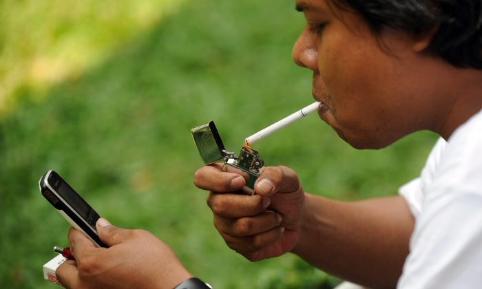 A man lights up a cigarette in Jakarta on Sept. 29, 2010 (Adek Berry/AFP/Getty Images)