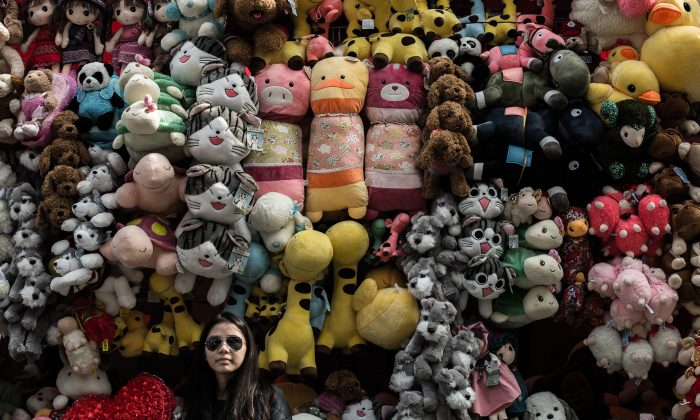A woman stands in front of a toy display in Hong Kong, Feb. 13, 2015. Chinese companies have been churning out too much merchandise, leading to falling prices—and a worried central bank. (PHILIPPE LOPEZ/AFP/Getty Images)