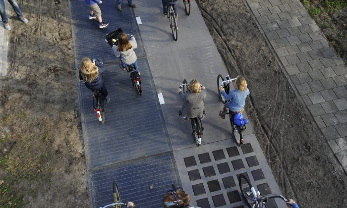 Cyclists use the SolaRoad, the first road in the world made of solar panels,  in Krommenie, the Netherlands (Solaroad)