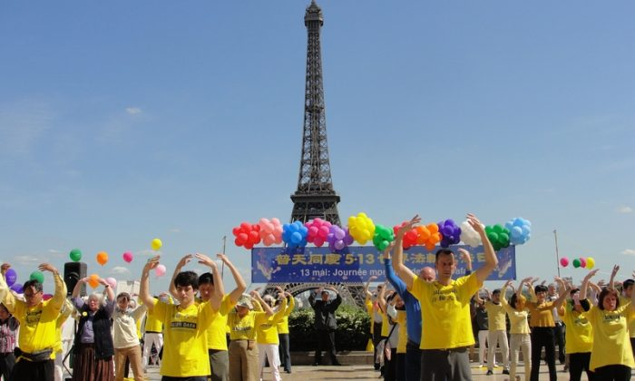 Practitioners from all ages demonstrate the exercises of Falun Dafa in front of the Eiffel Tower in Paris during World Falun Dafa Day on May 13, 2015. (Epoch Times)