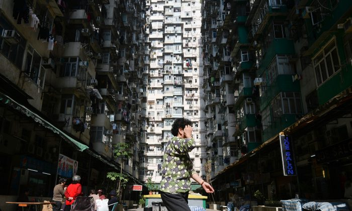 A woman walks through a residential estate in Hong Kong on December 30, 2013. China's real estate has stopped collapsing in April, but the situation remains precarious. (Dale de la Rey/AFP/Getty Images)