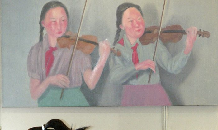 A woman takes a nap before an oil painting featuring two young pioneers playing violins at the Shanghai Spring Art Salon, 03 June 2004. (LIU JIN/AFP/Getty Images)