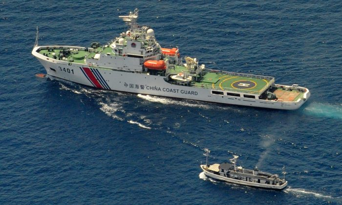 In this file photo, A China Coast Guard ship (top) and a Philippine supply boat engage in a stand off as the Philippine boat attempts to reach the Second Thomas Shoal, a remote South China Sea a reef claimed by both countries, on March 29, 2014. (Jay Directo/AFP/Getty Images)