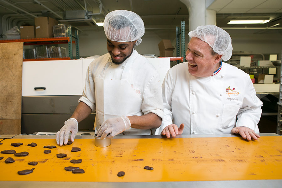 Jacques Torres with staff in front of the Chocolate Gingerettes. (Samira Bouaou/Epoch Times)