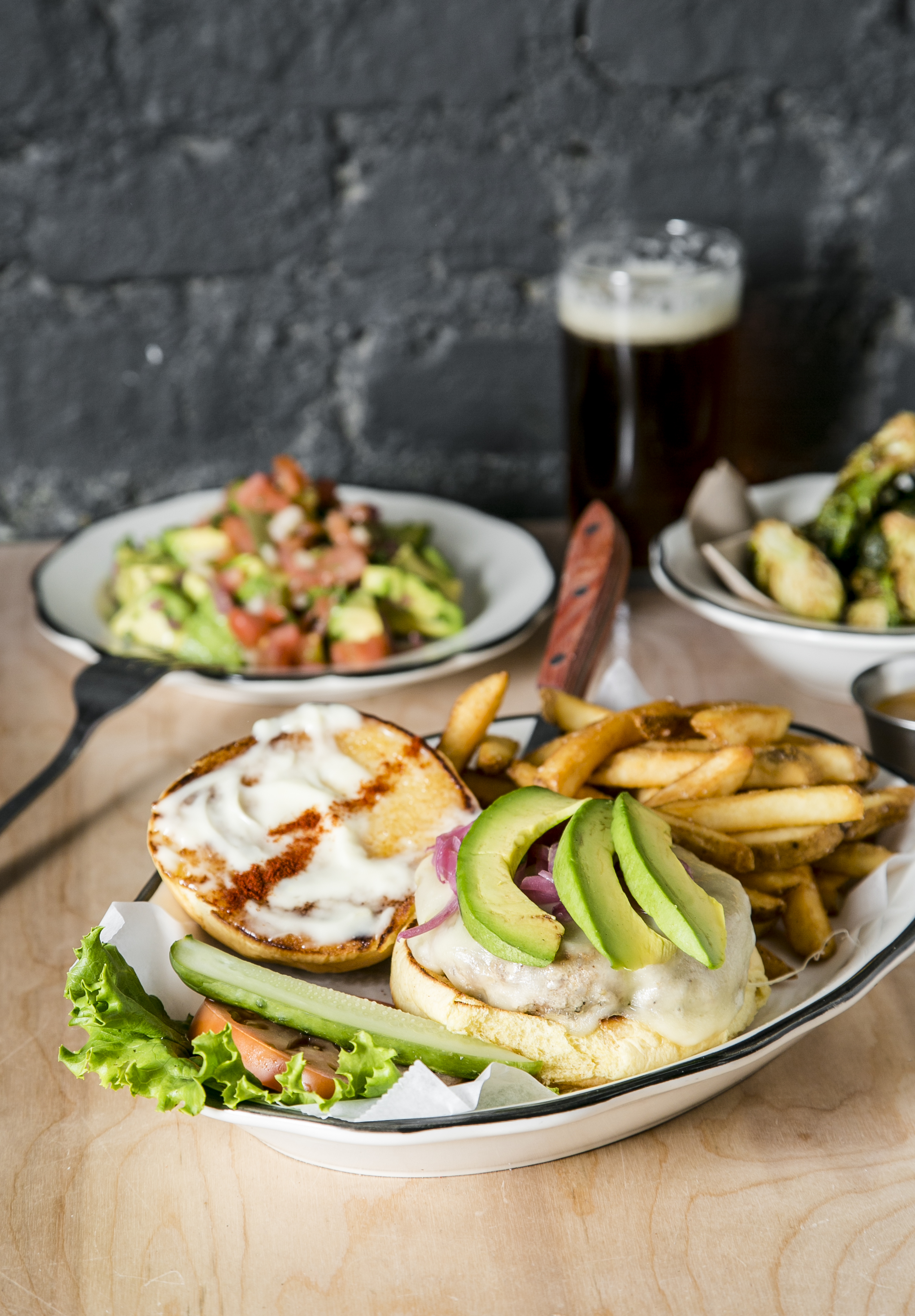The Californian, with organic turkey, avocado, truffle mayo, and lots of Swiss cheese; behind, a burger salad for those who prefer to go bunless. (Samira Bouaou/Epoch Times)