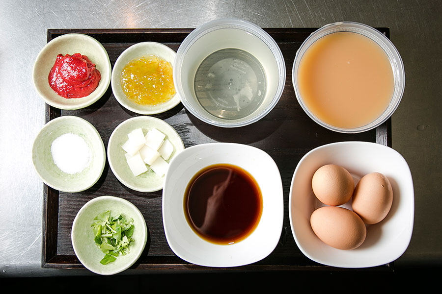 Chawanmushi ingredients. First row (L-R): Japanese plum paste, yuzu marmalade, Japanese-style stock, premixed egg mixture (eggs, Japanese-style stock, soy sauce, and salt). Bottom row: salt,  Japanese wild parsley, diced rice cakes, soy sauce, egg. (Samira Bouaou/Epoch Times)