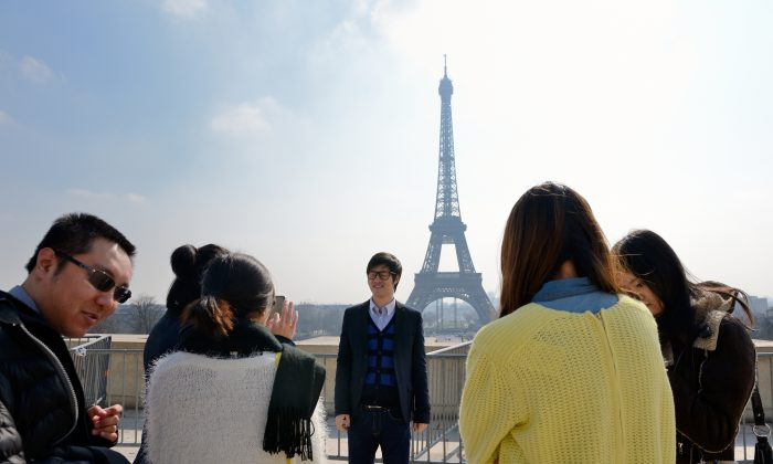 Chinese tourist take souvenir picturesin front of  of the Eiffel tower on March 27, 2013 in Paris. (Eric Feferberg/AFP/Getty Images)