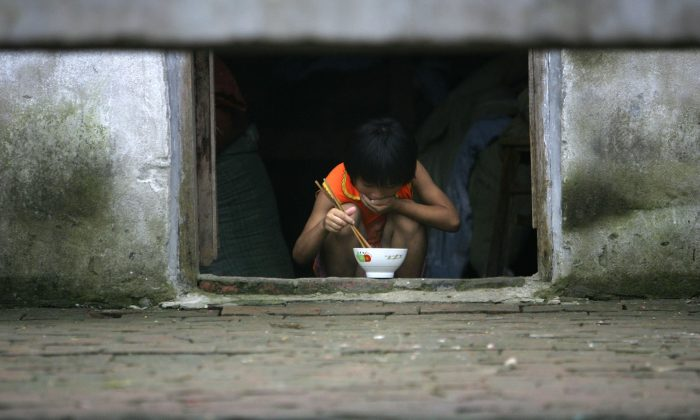 Nine-year-old Ding Shaonan has supper at Wang Jiayu Orphanage of Sanshilipu Village in Yingshang County of Anhui Province. China village child, left by their migrant parents, is subject to series of risk. The rape of minors, including boys, is getting more serious and the age of victims is getting younger. But the draconian law allows Communist perpetrators to avoid their due punishment. (Photo by China Photos/Getty Images)