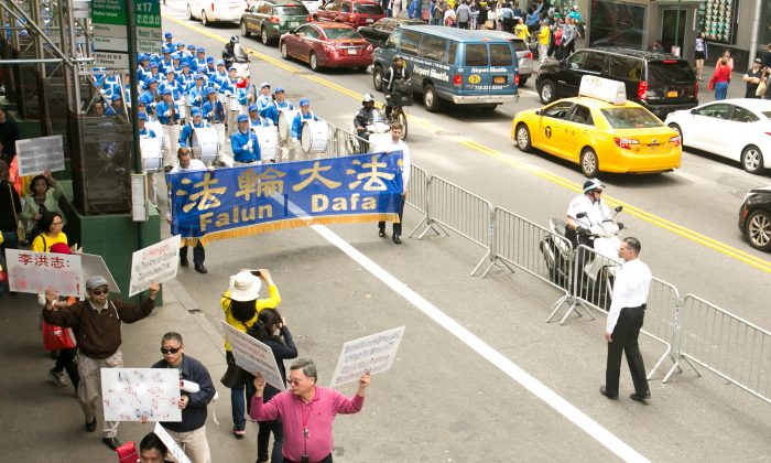 Over 8,000 Falun Gong practitioners participate in a grand parade for World Falun Dafa Day in 42nd Street, as Chinese Communist members walk in front with hate speech against the practice in Manhattan on May 15, 2015. This photo has been modified to remove the hate speech. (Benjamin Chasteen/Epoch Times)