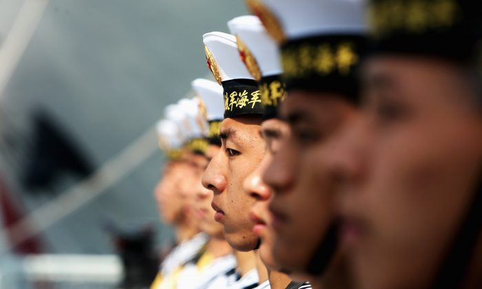 Chinese navy soldiers guard on Navy Battleship of Wenzhou at Qingdao Port on April 22, 2009 in Qingdao of Shandong Province, China. The Chinese regime is furthering its claims in the South China Sea with new civilian buildings. (Guang Niu/Pool/Getty Images)