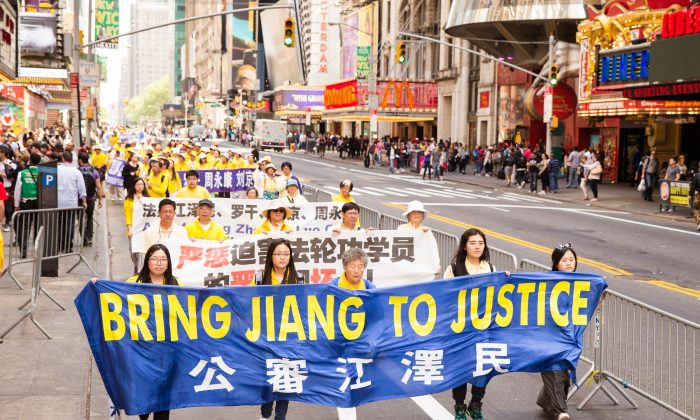 Falun Gong practitioners hold a banner in reference Jiang Ziemin, the previous leader of China who is responsible for conducting the persecution of Falun Gong, during a Falun Gong parade in Manhattan on May 15, 2015.  (Edward Dye/Epoch Times)