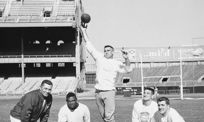 New York Giants quarterback Charley Conerly, veteran of two seasons with the pro football club, lets ball fly during a passing drill at Yankee Stadium in Bronx, New York, Nov. 6, 1958. Watching from left: Backfield coach Vince Lombardi, Fullback Mel Triplett, left halfback Phil King and right halfback Alex Webster. (AP Photo/John Lindsay)