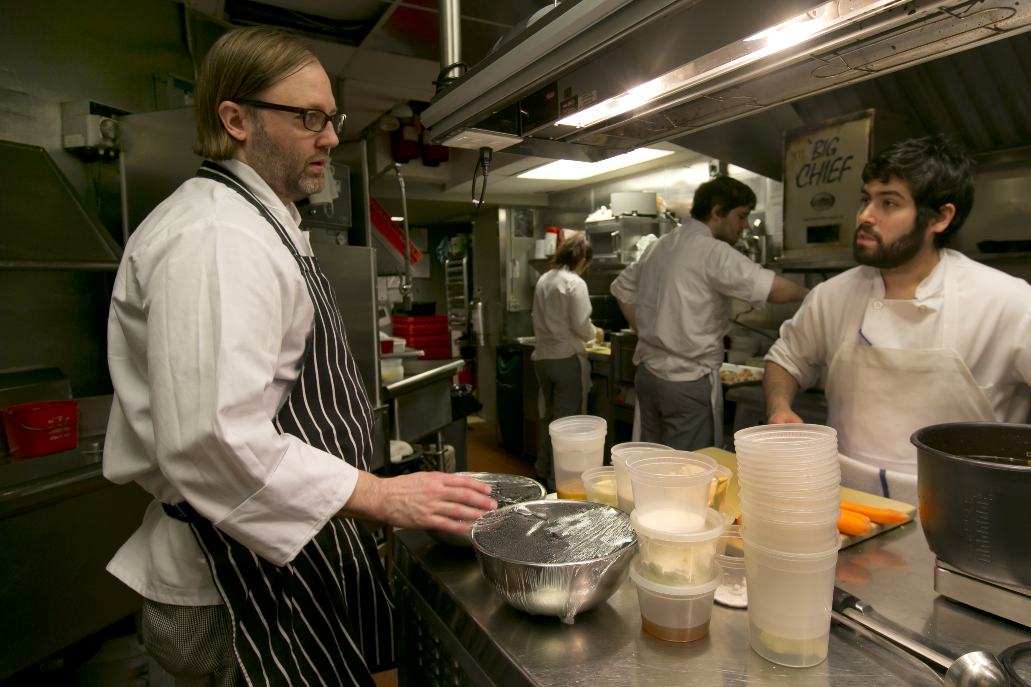 Chef Wylie Dufresne (L) talks with a member of his kitchen staff at Alder. (AP Photo/Richard Drew)