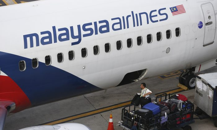 A Malaysia Airlines ground staff member unloads luggage from a plane at Kuala Lumpur International Airport in Sepang, Malaysia Monday, June 1, 2015. (AP Photo/Vincent Thian)