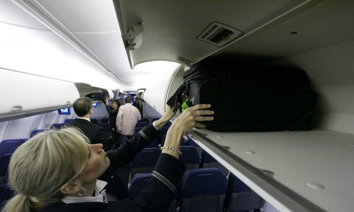 In this April 13, 2009 file photo, American Airlines flight attendant Renee Schexnaildre demonstrates the overhead baggage area. (AP Photo/Donna McWilliam, File)
