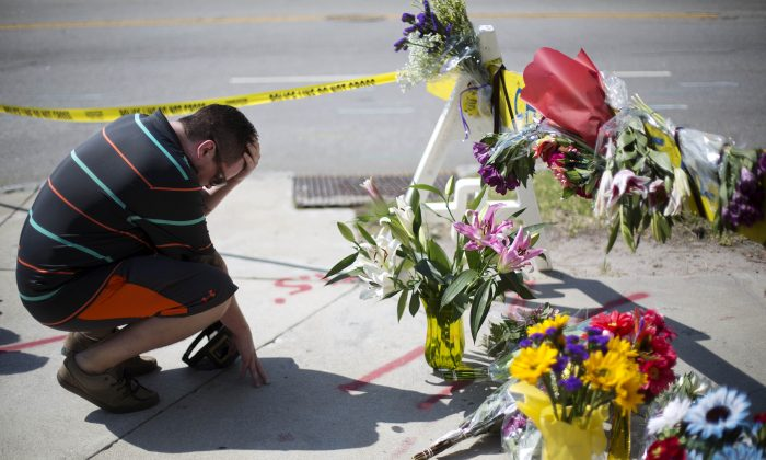 Noah Nicolaisen, of Charleston, S.C., kneels at a makeshift memorial down the street from where a white man opened fire Wednesday night during a prayer meeting inside the Emanuel AME Church killing several people in Charleston, Thursday, June 18, 2015. (AP Photo/David Goldman)