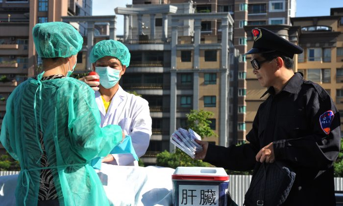 Falun Gong practitioners act out a scene of stealing human organs to sell during a demonstration in Taipei on July 20, 2014. (Mandy Cheng/AFP/Getty Images)