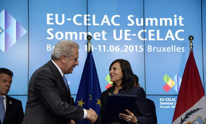 EU Commissioner for Migration, Home Affairs and Citizenship Dimitris Avramopoulos (L) shakes hands with Peru's Foreign Minister Ana Maria Liliana Sanchez Vargas de Rios following the signature of a bilateral visa waiver agreements between the European Union with Peru and Colombia during an EU-CELAC Summit held at the EU Council building in Brussels, June 10, 2015. (Thierry Charlier/AFP/Getty Images)