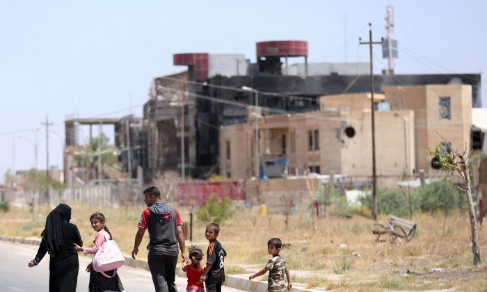 A displaced family walks towards their home in Tikrit, 80 miles (130 kilometers) north of Baghdad, Iraq. Civilians are trickling back into Saddam Hussein's hometown as they look to start anew, the consequences of a year under Islamic State rule conspicuously written on its charred buildings and damaged homes.(AP/ Hadi Mizban)