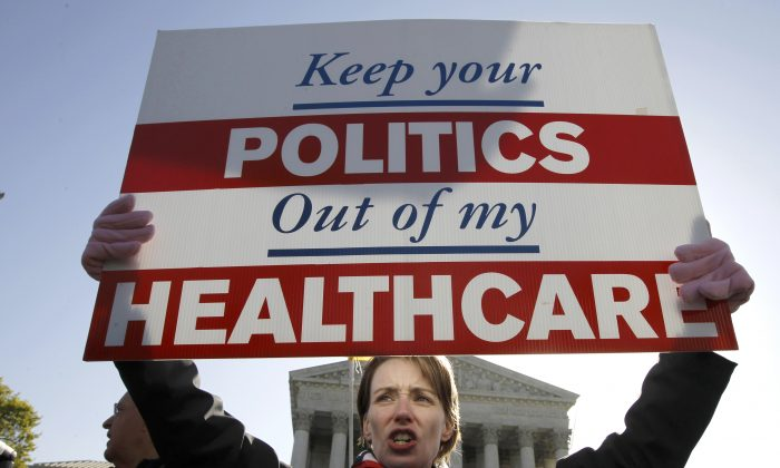 Amy Brighton from Medina, Ohio, who opposes health care reform, holds a sign in front of the Supreme Court in Washington, D.C., on March 27, 2012, during a rally as the court continues arguments on the health care law signed by President Barack Obama. (AP Photo/Charles Dharapak)