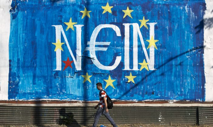 A man walks past a graffiti made by street artist N_Grams  that  read ''NO'' in German but also ''YES, IN'' in Greek language in Athens, on Sunday, June 28, 2015. (AP Photo/Petros Giannakouris)