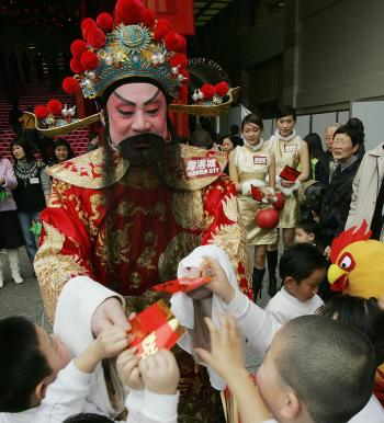A 'God of Fortune' hands out red packets at a huge shopping complex on the waterfront of Hong Kong. (Mike Clarke/AFP/Getty Images)