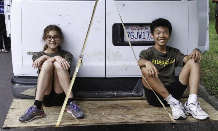 Aila Verheijke and Tanner Gao taking a break on the back of the Ride2Freedom van. (Chris Jasurek/Epoch Times)