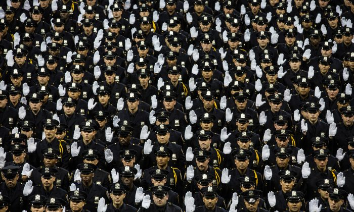 The 2014 class of the New York Police Department (NYPD) raise their hands while taking an oath at the NYPD graduation ceremony at Madison Square Garden, New York City, on June 30, 2014. (Andrew Burton/Getty Images)