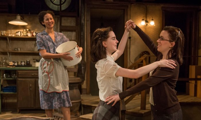 """A happy moment when 13-year-old Anne (Sophie Thatcher) dances with her older sister Margot (Lila Morse) while her mother Edith Frank (Kristina Valada-Vlars) watches, in the current Writers Theatre production of """"The Diary of Anne Frank.""""  (Michael Brosilow)"""