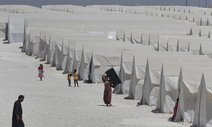 Syrian refugees walk around a refugee camp in Suruc, on the Turkey-Syria border, on June 19, 2015. Ahead of World Refugee Day on Saturday, June 20, 2015, the U.N. refugee agency, UNHCR, estimated that a total of 11.6 million people from Syria had been displaced by the conflict by the end of last year, the largest such figure worldwide. Turkey is the world's biggest refugee host with 1.59 million refugees, according to the most recent U.N. figures. (AP Photo/Emrah Gurel)