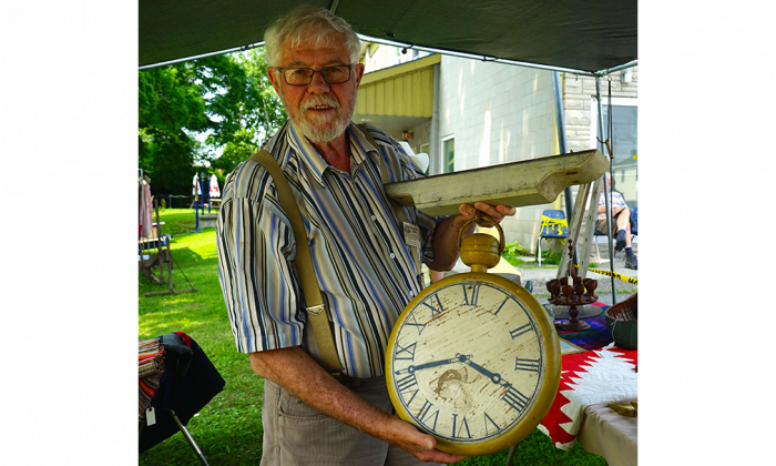 Collector, dealer, and antique show promoter Bill Dobson at his booth at the Perth Antique Show and Sale on July 4, 2015 in Perth, Ont. He is holding a wooden sign shaped like a watch that would have been hung outside a shop to indicate watch or clock repairs. (Pam McLennan/Epoch Times)