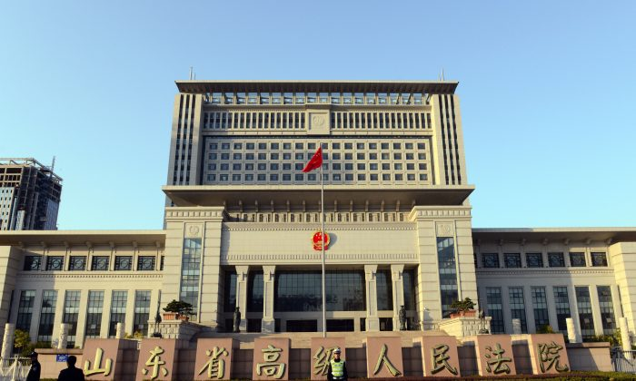 In this file photo, a Chinese policeman stands guard outside the Shandong high court building in Jinan, east China Shandong province on October 24, 2013. (Goh ChaiI Hin/AFP/Getty Images)