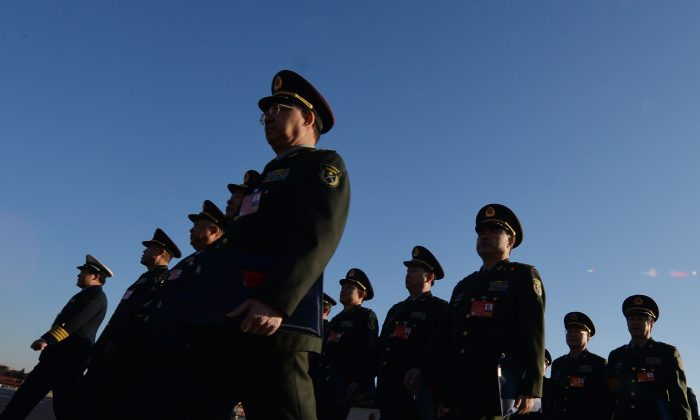 Military delegates arrive for the National People's Congress (NPC) at the Great Hall of the People in Beijing on March 5, 2014. China's new national security law passed by the National People's Congress (NPC) Standing Committee on July 1, 2015 is criticized and rejected. (Mark Ralston/AFP/Getty Images)