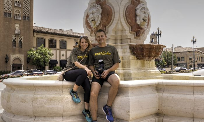Ride2Freedom cyclists Marton and Kata Baranyai, from Hungary, sit on one of the 200 fountains in Kansas City Missouri at the Country Club Plaza, June 27, 2015. (Cat Rooney/Epoch Times)