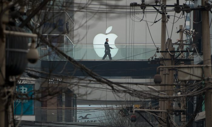 A man walks past an Apple logo displayed above a street at a shopping mall in Beijing on March 29, 2013. (Ed Jones/AFP/Getty Images)