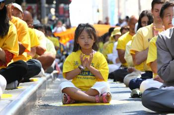 TINY MEDITATOR: A young Chinese girl meditates near Times Square on Saturday at a demonstration of the Falun Dafa exercises. (The Epoch Times)