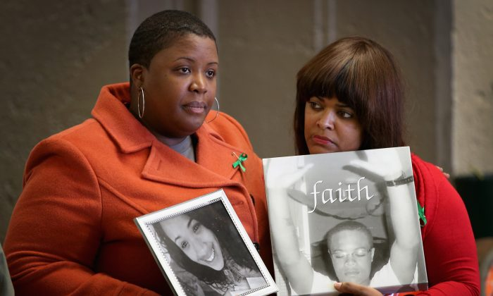 Cleopatra Cowley-Pendleton (L) holds a picture of her daughter Hadiya, 15, while standing with Shundra Robinson who is holding a picture of her son Deno Wooldridge, 18, in Chicago, on Dec. 14, 2013. Hadiya was shot and killed while hanging out with friends in a park after school on Jan. 29, 2013. Wooldridge was shot and killed while standing on his grandmother's porch on Oct. 18, 2010. (Scott Olson/Getty Images)