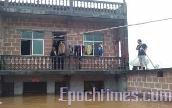 People trapped by the flood wait for rescue. (The Epoch Times)