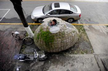 Dai Haifei, 24, from China's Hunan province, looks out from his egg-shaped mobile house where he has been living for the last two months, located near his office in Beijing on December 1, 2010. (Getty Images)
