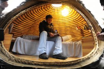 Dai Haifei, 24, from China's Hunan province, rests in his egg-shaped mobile house. (Getty Images)