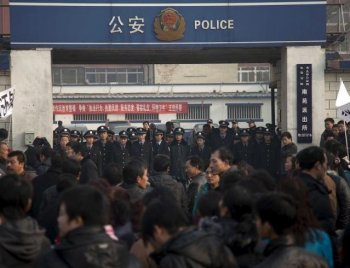 Security guards and policemen block the entrance of Nanyuna police station, in Beijing on December 22, 2010 as relatives protest outside after Chinese migrant worker Lu Xiaowu was stabbed to death while helping a friend to request back pay from his employer.  (STR/Getty Images)