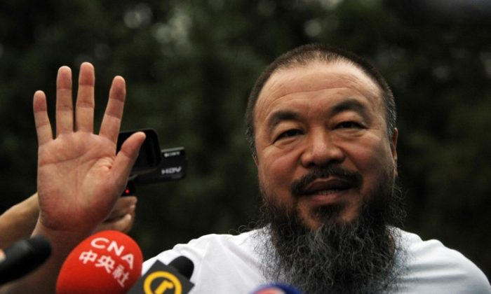 Outspoken Chinese artist Ai Weiwei waves to reporters outside his studio in Beijing on June 23.  (Peter Parks/AFP/Getty Images)