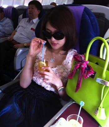 This photo, posted on the Internet in Beijing on July 5, shows Guo Meimei posing with one of her many designer handbags during a flight.  (STR/AFP/Getty Images)
