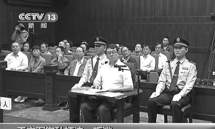 In a screen grab from a video released by Chinese Central TV, Wang Lijun is seen at his trial on Sept. 18, in Chengdu, China. The Chinese characters at the bottom of the image list the four charges against Wang. (The Epoch Times)