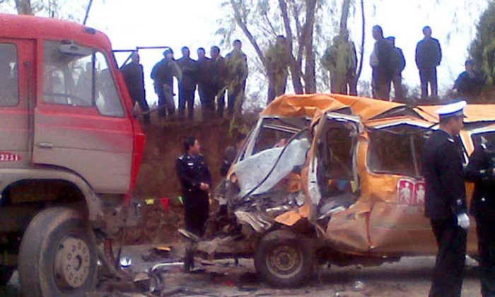 Police stand beside a damaged minivan school bus after it collided with a red truck on a road in the Yulinzi township in northwest China's Gansu Province on Nov. 16. Twenty people, 18 of them children, were killed in the head-on collision between the overloaded school bus and the truck, local authorities and state media said. (STR/AFP/Getty Images)