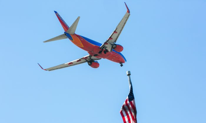 A Southwest Airlines jet flies over an American Flag before landing at the JFK airport in New York City on April 24, 2015. (Benjamin Chasteen/Epoch Times)