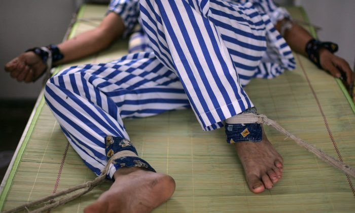 A mental patient lies in bed with arms and legs being bound at the Anxian Mental Hospital, in Sichuan Province, China, on Aug. 24, 2008. Beginning in 2000, the Chinese regime began the widespread use of mental hospitals to detain and punish dissidents. (China Photos/Getty Images)