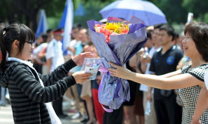 """A mother greets her daughter who finished the first day of difficult college entrance exams, or """"gaokao,"""" in Beijing. Current policies make it more difficult for students born in rural provinces to enter prominent universities, even if their parents work and live in an urban area. (STR/AFP/GettyImages)"""
