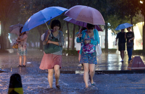 Two women cross a flooded street during heavy rainfall in Beijing on July 21, 2012. (Ed Jones/AFP/Getty Images)